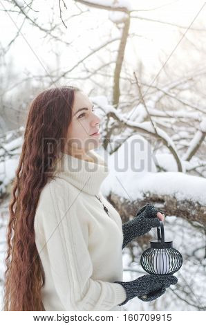 Long-haired brunette girl walking in a winter forest with a lantern