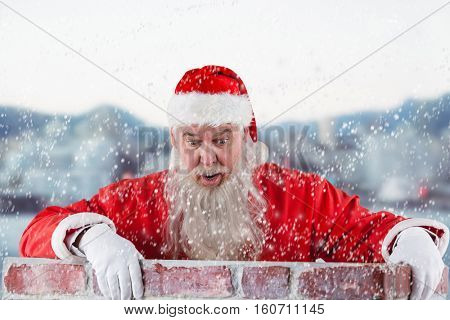 Santa Claus peeking over wall against blur view of harbour