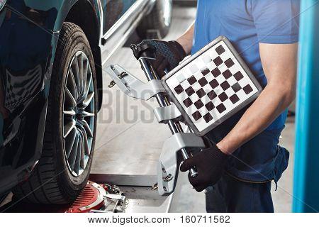 Grid sensor sets mechanic on auto. Car on stand with sensors wheels for alignment camber check in workshop of Service station