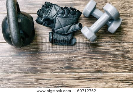 Sport background with copyspace. Top view of grey dumbbells black kettlebell and workout gloves. Weight lifting exercise concept.