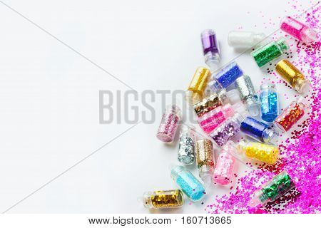 Multicolored sparkles for manicure and make-up in transparent bottles on a white background place for text and selective focus