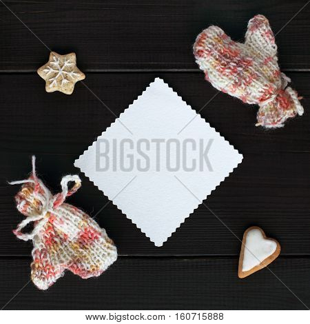 clean patterned sheet surrounded by knitted mittens and figured cookies top view / for the heart and warm greetings