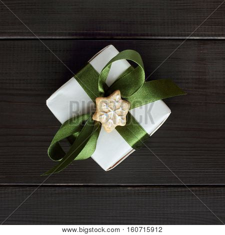 holiday gift tied up by green ribbon with bow lying on dark wooden surface top view / surprise with hint winter
