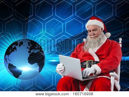 Santa sitting on chair and using laptop against digitally 3D generated background