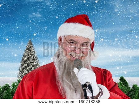Portrait of santa singing christmas song on microphone against digitally generated snowy background