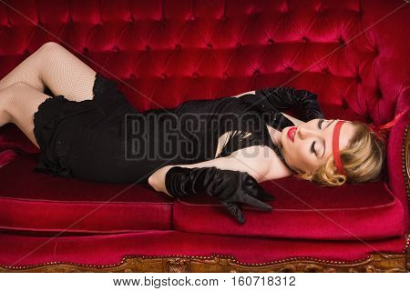 Elegant Young Woman In Retro Style Lying On A Sofa.