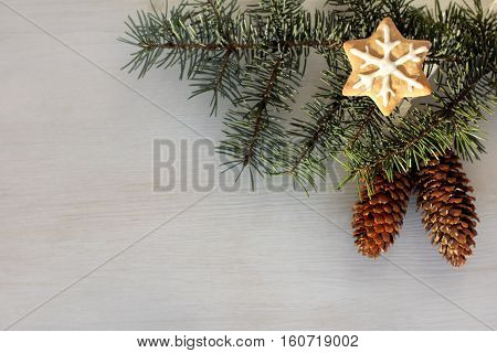 fir branches with pine cones and ginger snowflake on a light wood surface top view / festive decoration winter holidays