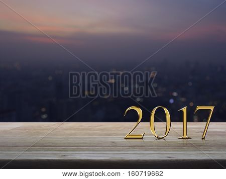 Happy new year 2017 gold metal text on wooden table over blur aerial view of cityscape on warm light sundown