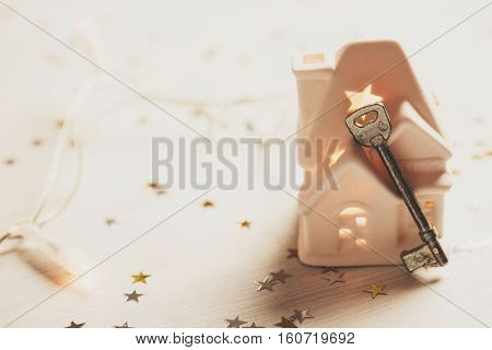 Small white house with a roof, lights and key standing on wooden background with sparkles. Space for text