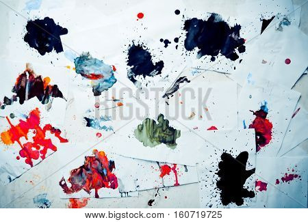 Many red colored blots on white paper with streaks. Abstract creative spots of paint on a white background. Red bright colors. Stained-spattered table