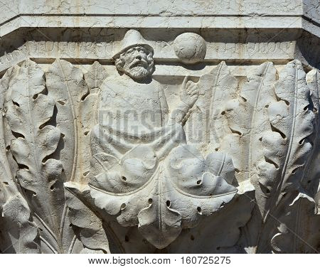An astrologer point at the stars and planets. A medieval relief on Doge Palace outer portico in Venice