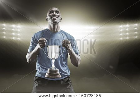 Happy athlete holding trophy looking up against spotlight 3D