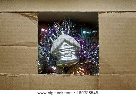 Vintage glass small house in cardboard box on background of other shiny Christmas toys.