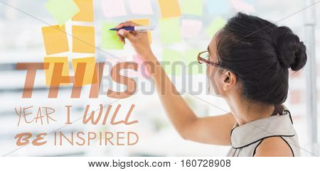 this year i will be inspired against side view of smiling designer writing on sticky notes at window