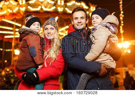 Couple with children on hands in xmas on street at night