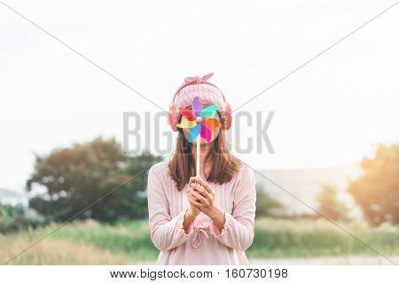 Beautiful Girl Holding Wind Toy Or Wind Turbine Or Pinwheel And Wool Hat At Meadow On Winter Season