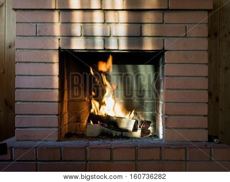 The brick fireplace firewood. Burning fire. Bright flames