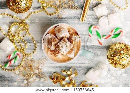 Cup of milk with marshmallows and cocoa with golden Christmas decorations cozy New Year background top view