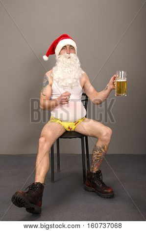 Santa Claus with tattoo holding glass with beer and cigarette on grey background