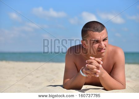 Man On Beach Lying In Sand Looking To Side. Young Male Enjoying Summer Travel Holiday Resting On The