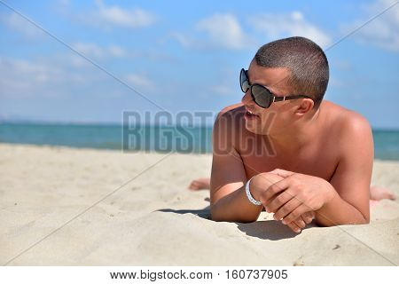 Man With Sunglasses On Beach Lying In Sand Looking To Side. Young Male Enjoying Summer Travel Holida