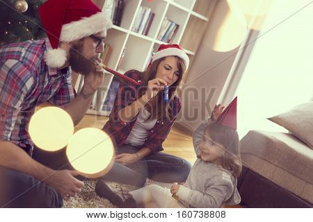 Beautiful young family sitting next to a nicely decorated Christmas tree wearing Santa's hats and blowing party whistles. Focus on the mother