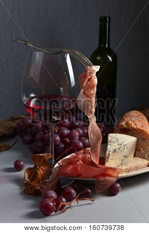 Jamon , Cheese , Grape And Red Wine On The Kitchen Table
