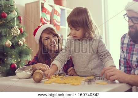Beautiful young family having fun while baking a Christmas cookies. Focus on the mother