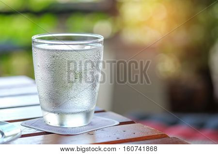 Water glass on wooden table with blurred background.