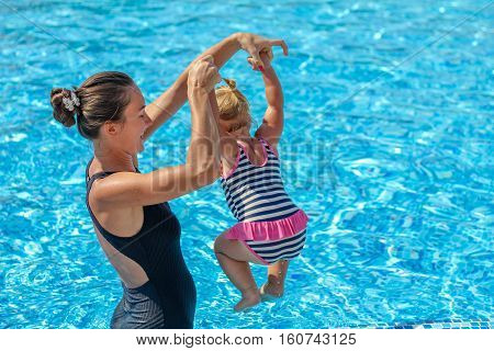 Baby Girl Learn To Swim In Pool  With Her Mother
