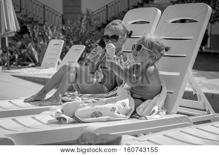 Black And White Photo Of Baby Girl Eating Ice Cream Near The Pool