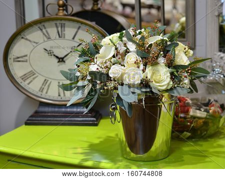 Bouquet of roses in a metal bucket on a brilliant green table on a background of old clocks and mirrors.