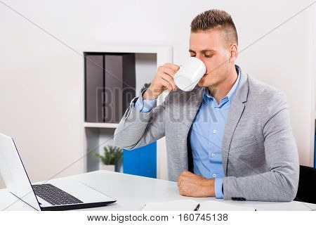 Businessman is drinking coffee at his office.