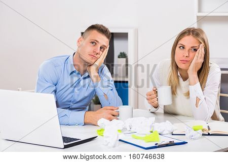 Exhausted businessman and businesswoman drinking coffee at their office.