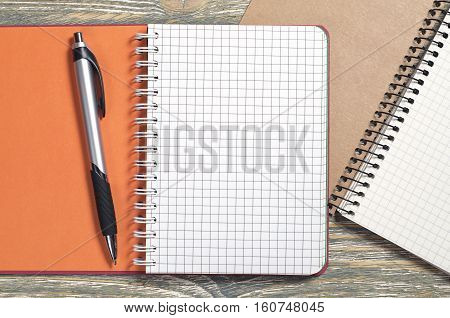 Opened notepad and pen on old wood background top view
