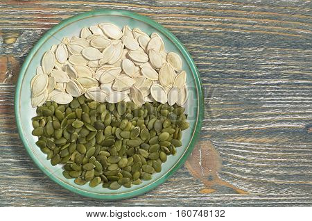 Pumpkin seeds peeled and in the shell in plate on old wooden background top view