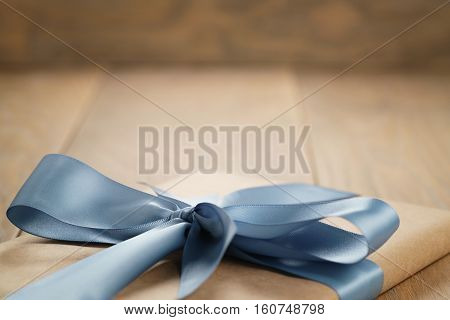 handmade gift brown paper box with blue ribbon bow on wood table, closeup photo