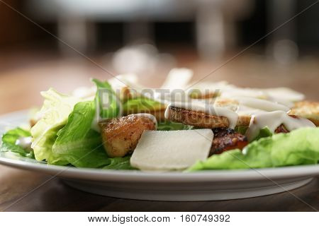 plate with fresh caesar salad with chicken on old wooden table, shallow focus