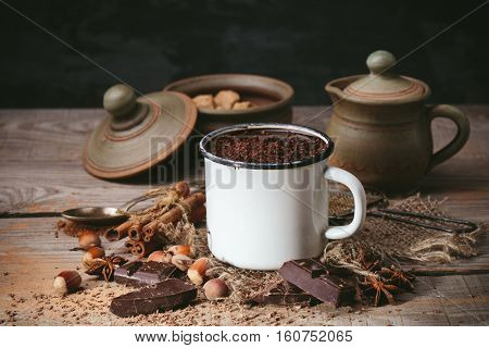 cup of hot chocolate, cinnamon sticks, nuts and chocolate on wooden table