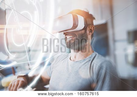 Concept of digital screen, connection and interfaces.Smiling hipster enjoyingvirtual reality glasses in modern design home studio.Smartphone use with VR goggles headset.Horizontal, flare, blurred
