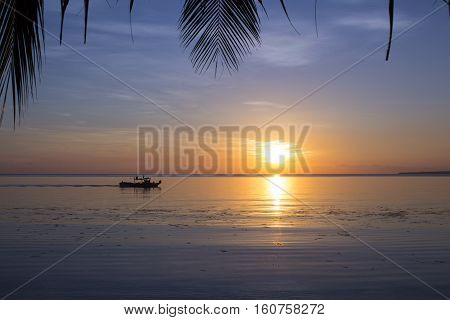 Sea sunset with palm leaves. Idyllic tropical lagoon with a boat. Exotic beach view to orange sunset. Romantic wedding place photo. Small fisherman's boat silhouette in ocean. Travel banner template