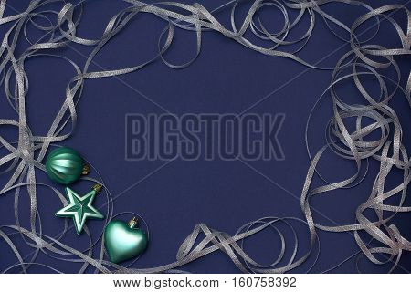 Frame with silver ribbon scrollwork. Christmas toys star, balls, heart turquoise color. New Year decorations. Dark blue background, top view, flat lay, copy space