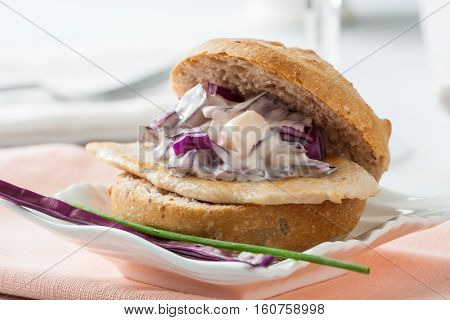 Streetfood: delicious chicken and cabbage sandwich on a plate.