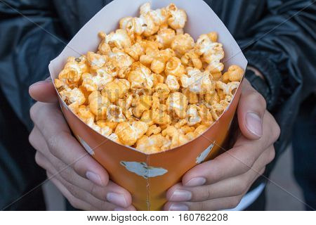 Boy Hand Holding Bucket Of Popconrn Or Popcorn Bowl. Favorite Street Food In India.