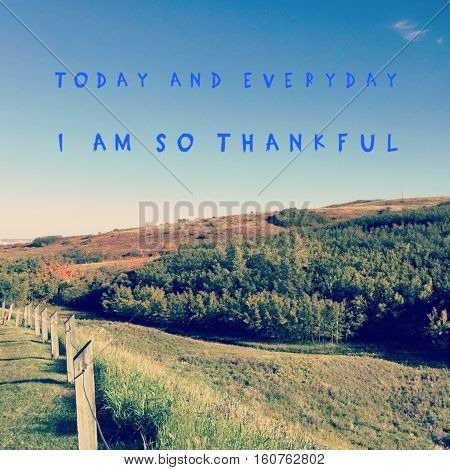 Inspirational quote on bright clear blue sky over meadow in autumn with hills and forest trees background. Grass and fence posts in foreground. Today and everyday I am so thankful.
