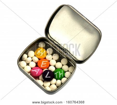 White and color pills with letters in metallic pillbox as the concept of health care
