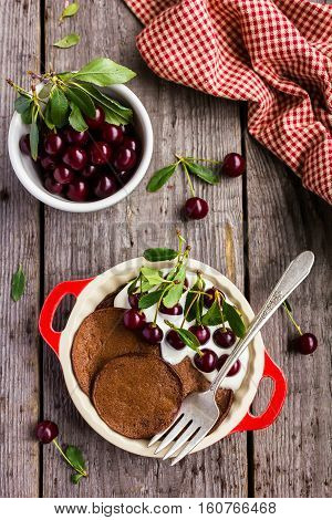 Chocolate pancake with sour cream and sweet cherry for breakfast or pancake day, top view