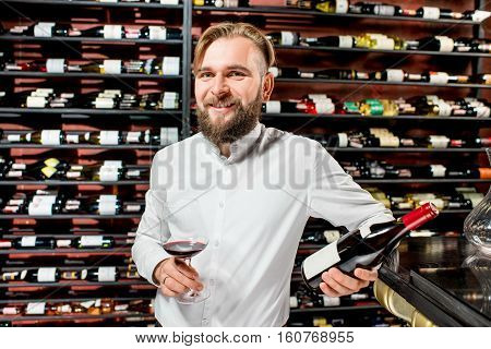 Portrait of a handsome sommelier with glass of wine in front of the shelves with bottles at the luxury supermarket or restaurant