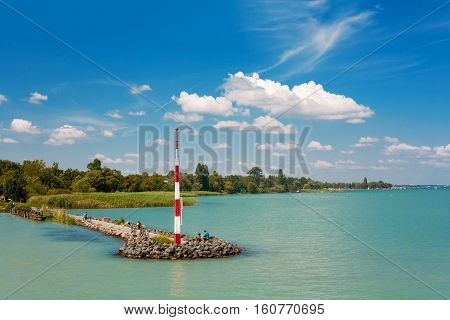 View of Lake Balaton with a stone pier and small beacon in Hungary