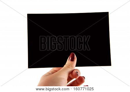 Manicured female hand holding a blank black paper. Isolated on white background.